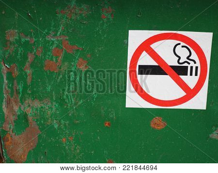 prohibiting the sign not to smoke on a rusty sheet of iron