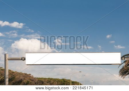 Large rectangular blank billboard crossing the street with sky and trees on backgroun