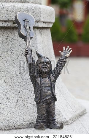 WROCLAW - POLAND, JUNE 12, 2017 : Wroclaw dwarf, small fairy-tale bronze figurine on the side walk, guitarist, Wroclaw, Poland. There are over 350 dwarfs spread all over the city, they are a big tourist attraction