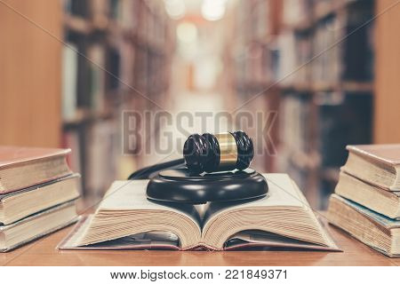 World book and copyrights day and international legal rights concept with old book in library with judge gavel on open law textbook in court archive text collection study room