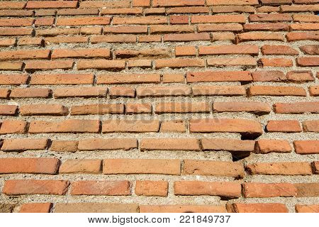 Background of a wall made of old clay solid bricks and concrete, view from below. Italy