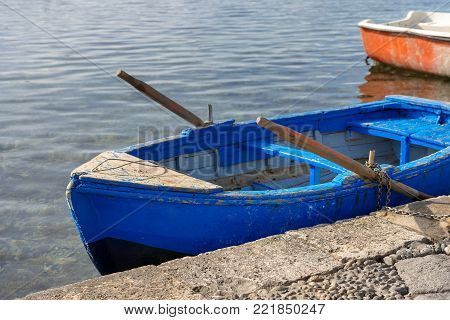 Old blue wooden rowing boat moored in the port. Marzamemi, Syracuse (Siracusa) - Sicily island, Italy