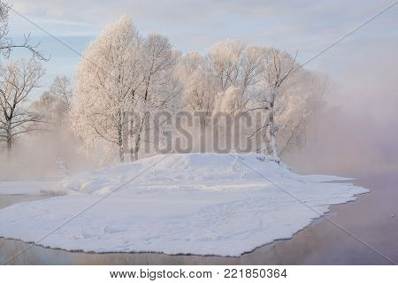 Snowy frozen landscape of sunrise on lakeside with trees