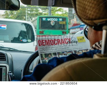 Yangon, Myanmar - Feb 27, 2016. Driver reading news in car in Yangon, Myanmar. Yangon also called Rangoon city capital of independent Myanmar (Burma) from 1948 to 2006.