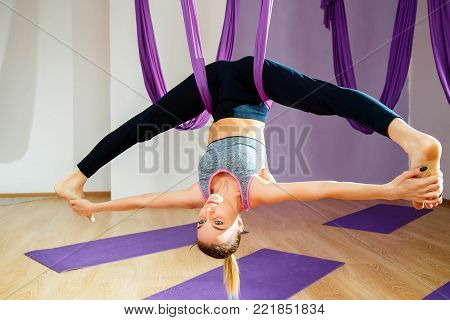 Young woman doing stretching and twine. Aerial yoga exercise or antigravity yoga indoor. Fitness, stretch, balance, exercise and healthy lifestyle people. Woman using hammock.