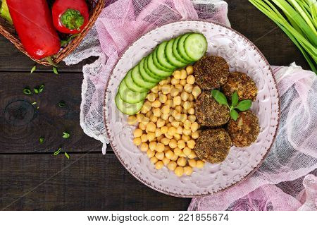 Tasty meat cutlets, chickpeas, fresh cucumber on a ceramic plate on a dark wooden background. The top view