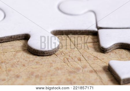 close up of a white jigsaw/puzzle with one gap, over wooden table background, symbol of problem solving