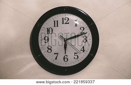 Closeup view of an old retro clock on white wall.