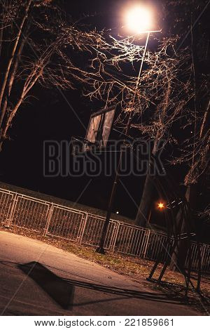 Basketball hoop in dark, illuminated by basketball yard lights.