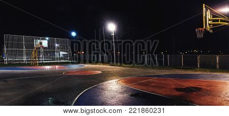 Street basketball yard by night, outdoor scene.