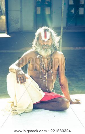 Jaipur, India - 2014, December 29 : A holy man or sadhu sitting in the courtyard of a Hindu temple in the center of Jaipur in Rajasthan