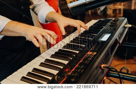 a musical synthesizer to which the hands of a man touch