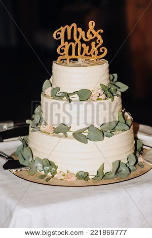 wedding cake three tiers decorated with flowers on a stand