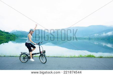 Cheerful young lady riding the bicycle on the lakeside in the morning