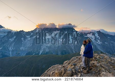 Couple of people looking at the sunrise over Mont Blanc mountain peak (4810 m). Valle d'Aosta, italian summer adventures and travel destination on the Alps.