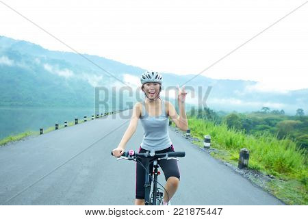 Cheerful sport girl cycling on the lakeside in the morning