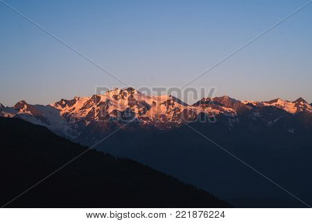 Mountain summer landscape at pink sunset over high snow peaks. Caucasus.