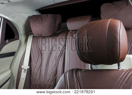 Modern Luxury car inside. Interior of prestige modern car. Comfortable leather seats. Red and white perforated leather. Back passenger seats.  Modern car interior details