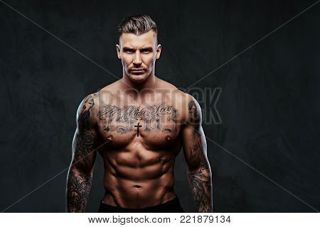 Portrait of a tattooed muscular shirtless man with stylish hair posing at the camera on a dark background.
