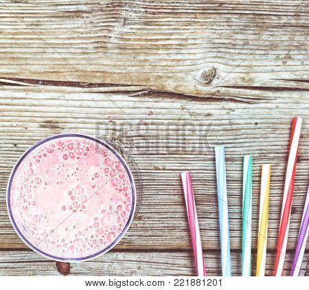 Strawberry shake with yogurt and cocktail colored tubules on an old board. Spring detox. Summer time. Healthy eating. Healthy food