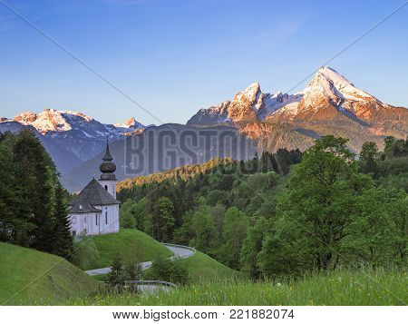 Spring serene scenery with snow-crowned tops of Watzmann mount and Maria Gern church in German national park Berchtesgaden