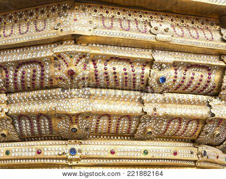 Fragment of the Indian chariot in the Krishna temple with a lot of precious stones. Macro view of sapphire, ruby, emerald, diamond on the surface of a very expensive carriage, which is used for religious ritual holidays