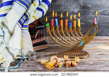 jewish holiday Hanukkah with menorah traditional Candelabra and wooden dreidels spinning top retro