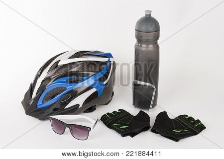 Bike accessories, bike helmet, bike gloves, eyeglasses and water bottle in holder.
