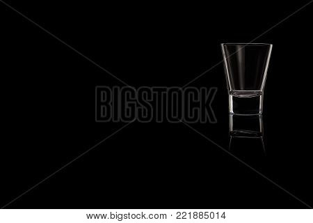 A small shot glass of tequila, vodka or whiskey on a black background. Place for your text.
