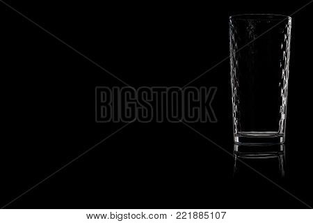 Faceted empty glass of water on a black background. Place for your text.