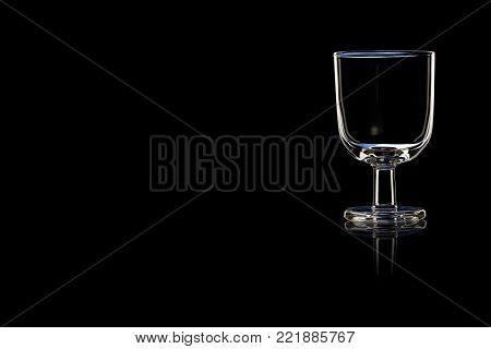 An empty glass of port or sherry on a black background. Place for your text.