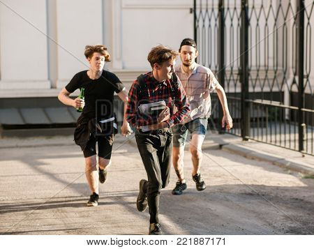 stressed smart geek running away from street gang thugs. teenage bullying. chase concept