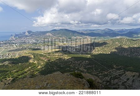 Panorama of the Sudak valley and the resort town of Sudak. View from the top of the mountain Ai-George. Beginning of September.