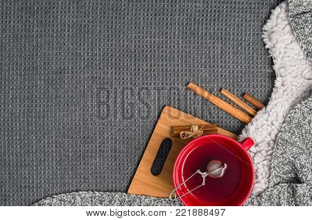 Mug with tea and home decor on grey, cosy blanket background. Winter morning relax concept, top view. Frame with cup and copy space around objects.