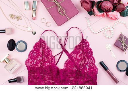 Fashion collection with sexy red lace lingerie, accessories, flowers, cosmetics and jewelry on pink background, copyspace. Womens Day concept, top view
