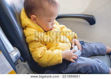 Cute little Asian toddler baby boy child wearing & fasten seat belts while sitting on airplane seat. Safety measures on board. Precautions on plane during flight for kid