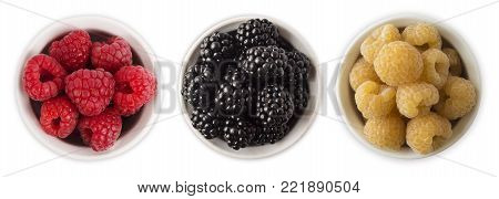 Black, red and yellow berry in a bowl isolated on white background. Raspberries and blackberries on white background. Vegetarian or healthy eating. Red and white raspberries and blackberries with copy space for text. Top view.