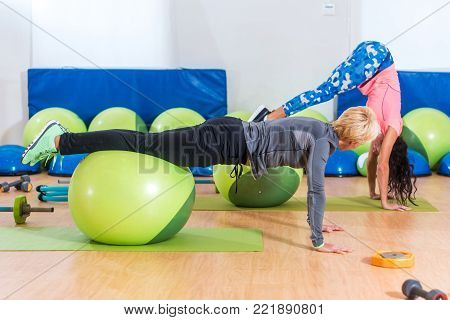 Slim young Caucasian women exercising doing stability ball roll outs with pull-in or handstand in a gym.