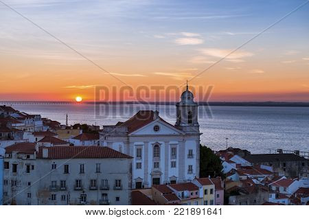 View of a Church in the Alfama neighborhood from the Portas do Sol viewpoint at sunrise in Lisbon, Portugal; Concept for travel in Portugal, visit Portugal and most beutiful places in Portugal