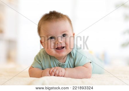 Very happy laughing newborn baby in blue clothes lying on his belly.
