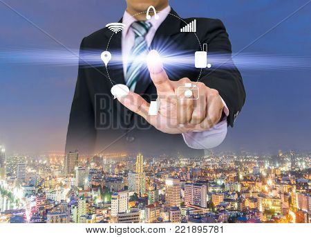 Businessman hands press the button pushing icon of touch screen on city view