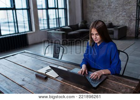 Front view of a smiling student girl chatting on her laptop.