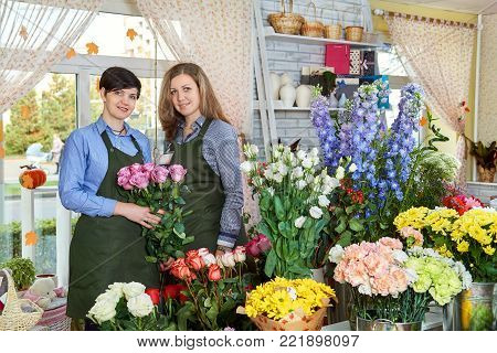Women flower sellers. Two attractive young women working in flower shop and enjoying in beautiful flowers. Female sales assistant working as florist and holding bouquet with with roses.