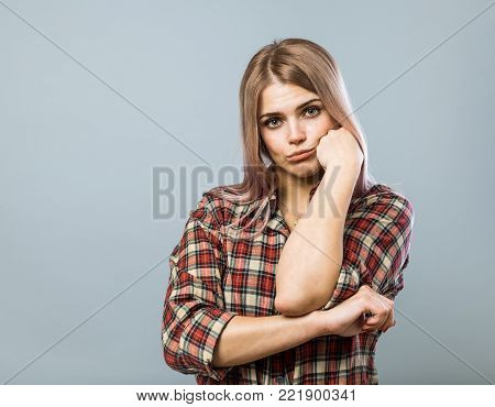 Young cute woman in sadness on grey