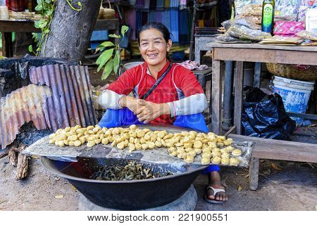 Siem Reap, Cambodia - January 03, 2017: A smiling girl selling palm sugar at producers village. Palm sugar is a sweetener derived from any variety of palm tree