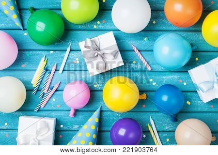 Party birthday table. Colorful balloons, gifts, confetti and carnival cap on blue table top view. Holiday supply.
