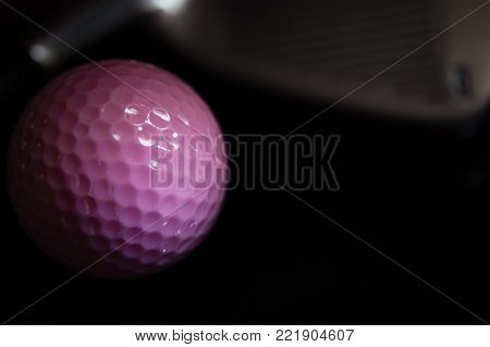 Horizontal low key close up image of pink golf ball with metal putter blurred in a black background