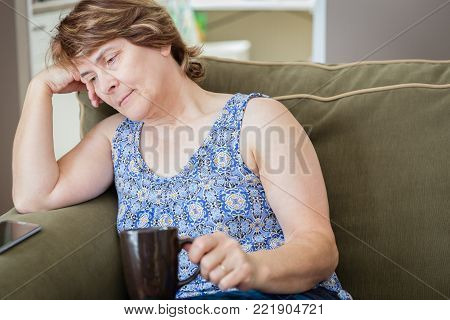 horizontal head shot of sad and depressed caucasian woman holding a cup of coffee.