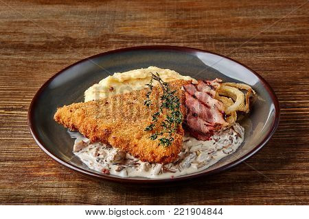 Chicken schnitzel with herb, mashed potatoes and mushrooms sauce on plate on wooden table background. Healthy food. Copy space. Still life. Served at restaurant, cafe, bar, pub