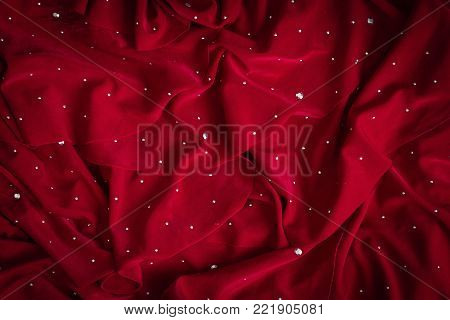 horizontal image of a blank deep red cloth background with shiny studs embedded great for a Christmas theme.